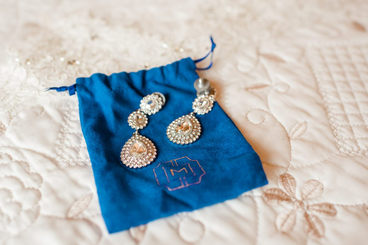 large earrings on a velvet blue bag
