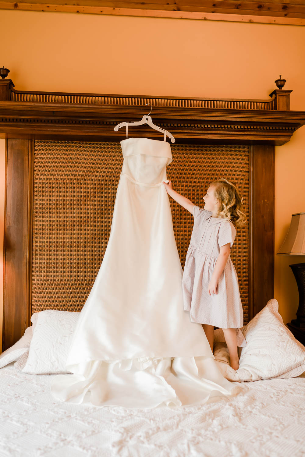 small child looking up at a wedding dress hanging above a bed