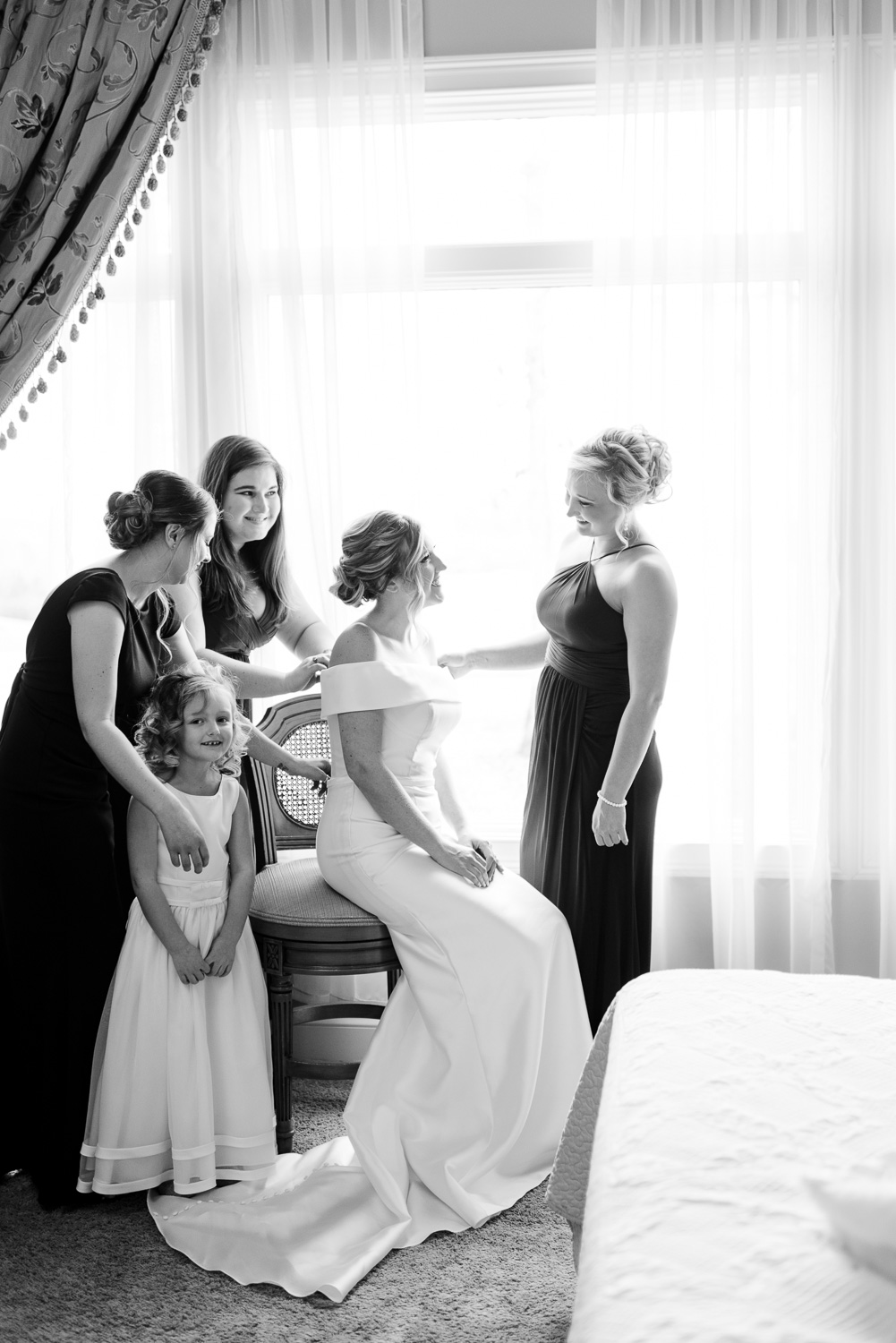 bride and her bride's maids around her in front of a large window.