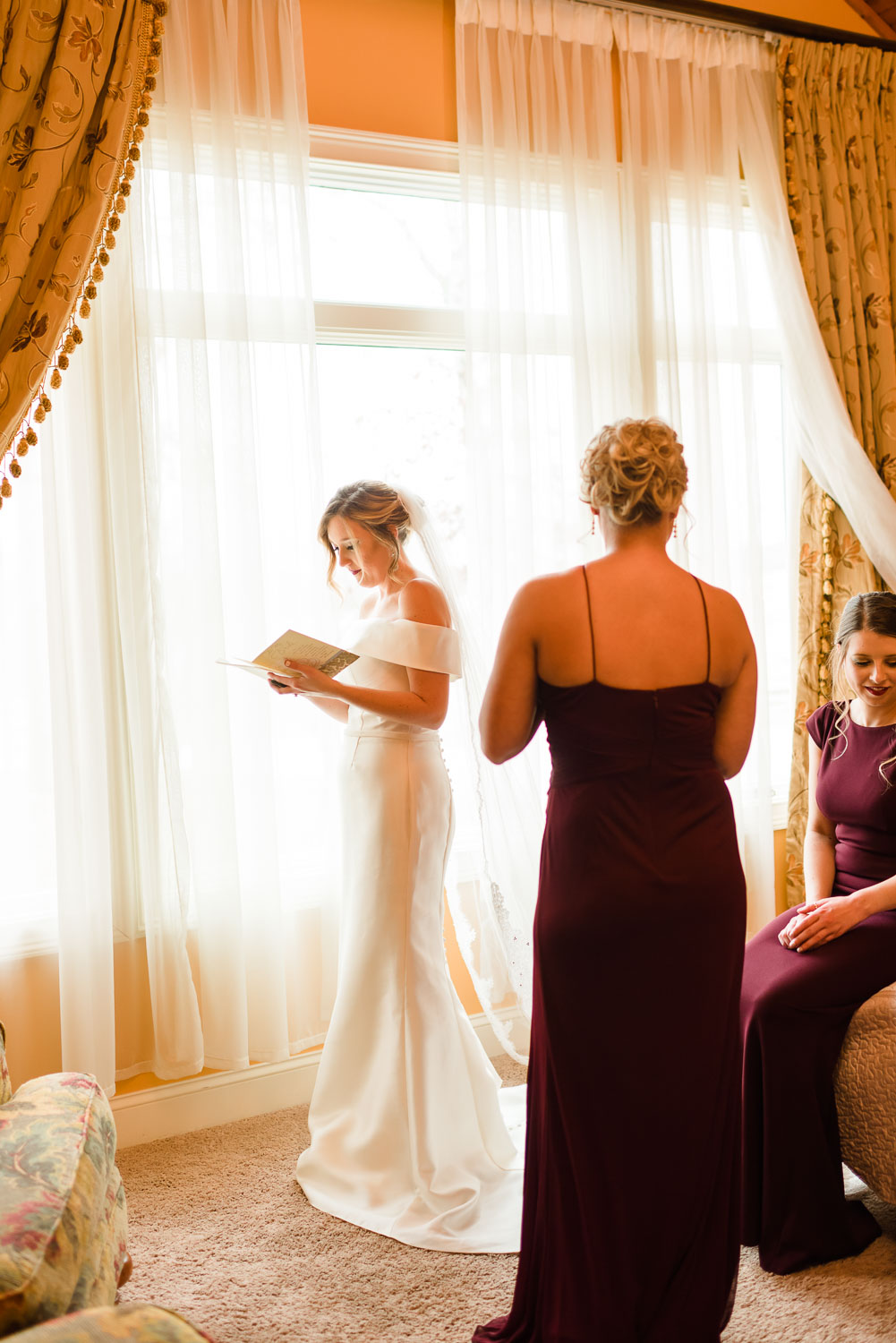 bride standing in front of a window reading a letter from her fiance on her wedding day.