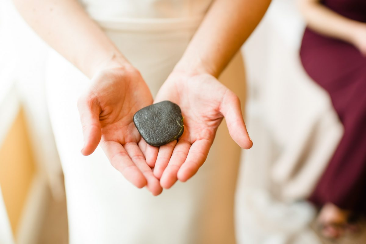 woman's hands holding a rock from whitewater rafting in Tennessee.