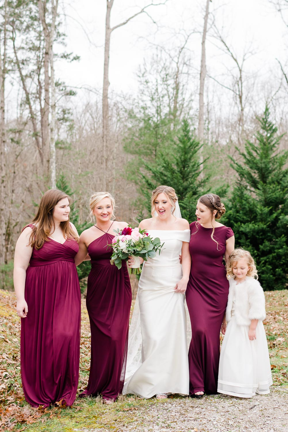 bridesmaids and bride wearing burgundy dresses and flower girl in white fur jacket.