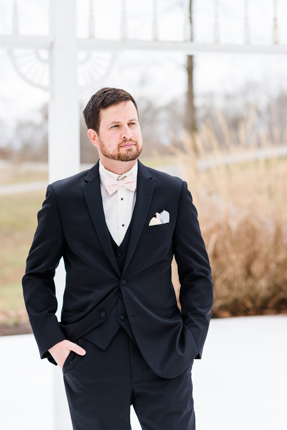 groom wearing a black suit waiting outside at a gazebo.