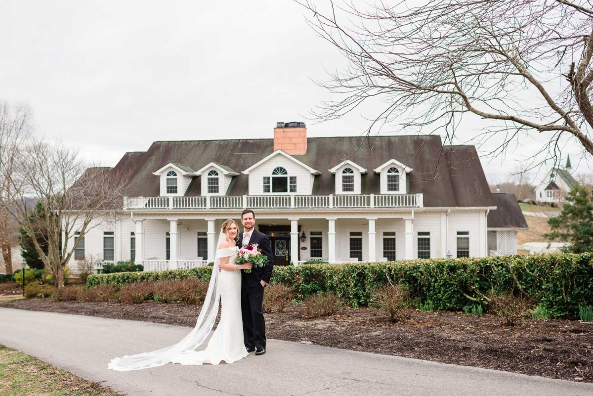 Whitestone inn farm house venue with a bride and groom in front.