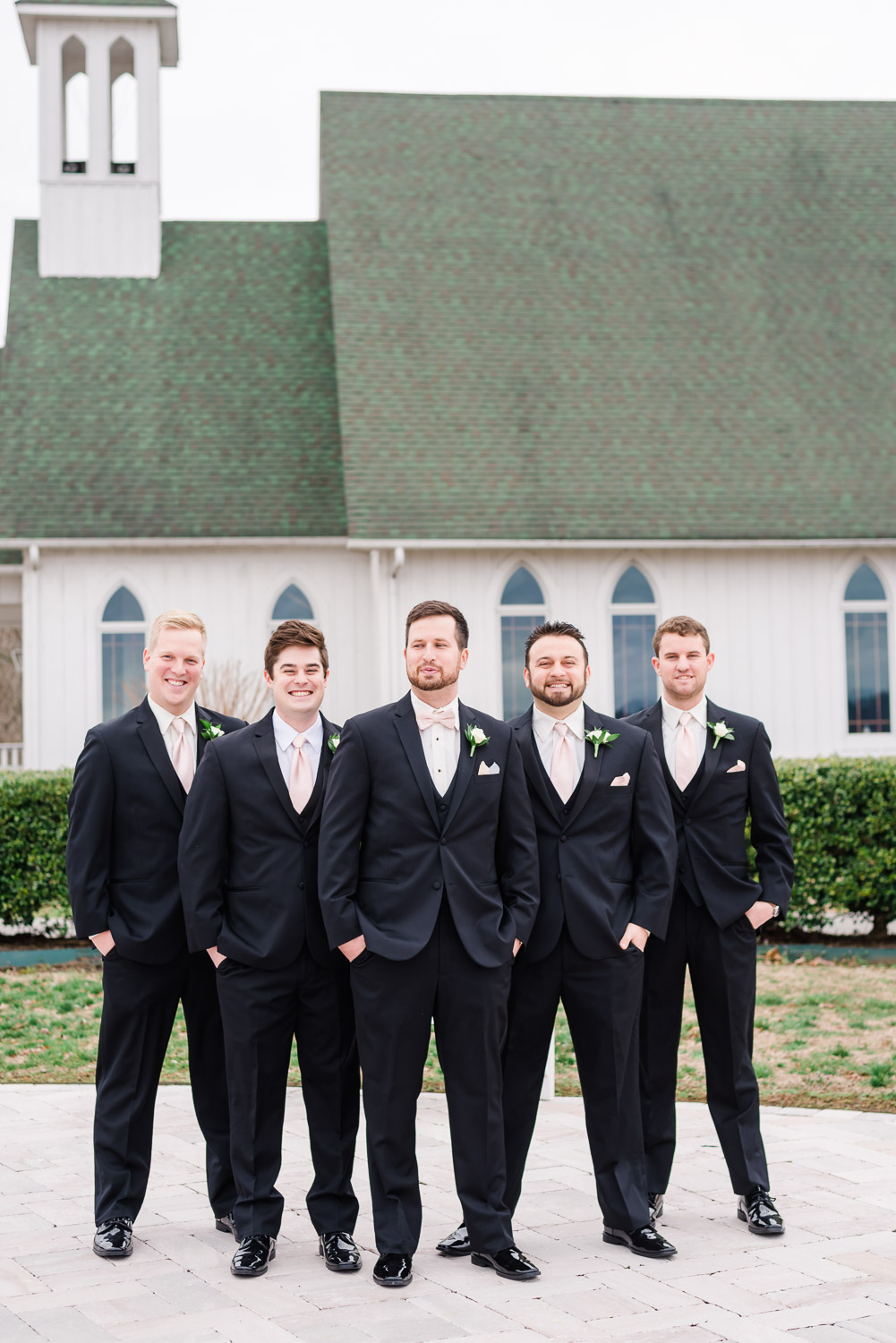 groomsmen outside of the church at Whitestone country Inn wearing black suits and pink bowties