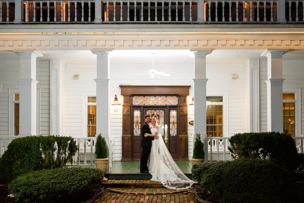 bride and groom on front steps at Whitestone Inn at night.