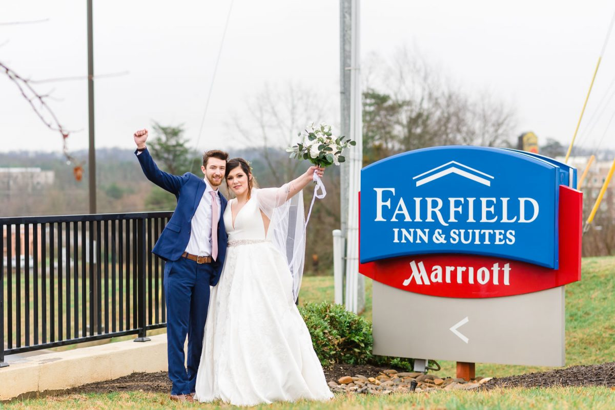 wedding couple standing next to Fairfield Inn sign on snyder and Campbell station road in Knoxville