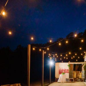 outdoor beer garden under bistro lighting and blue night sky