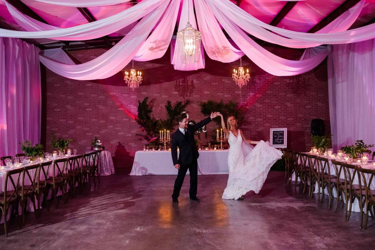 indoor wedding reception venue with pink uplighting