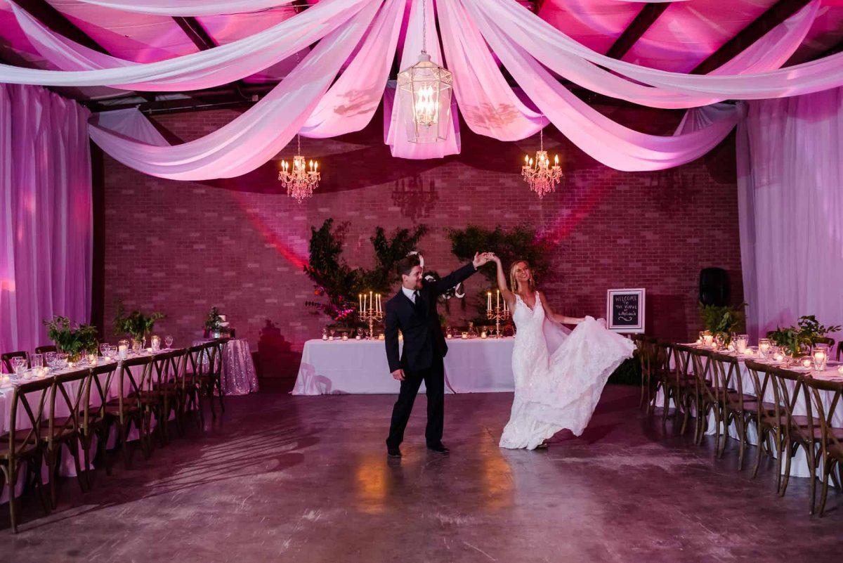 indoor wedding reception venue with pink uplighting