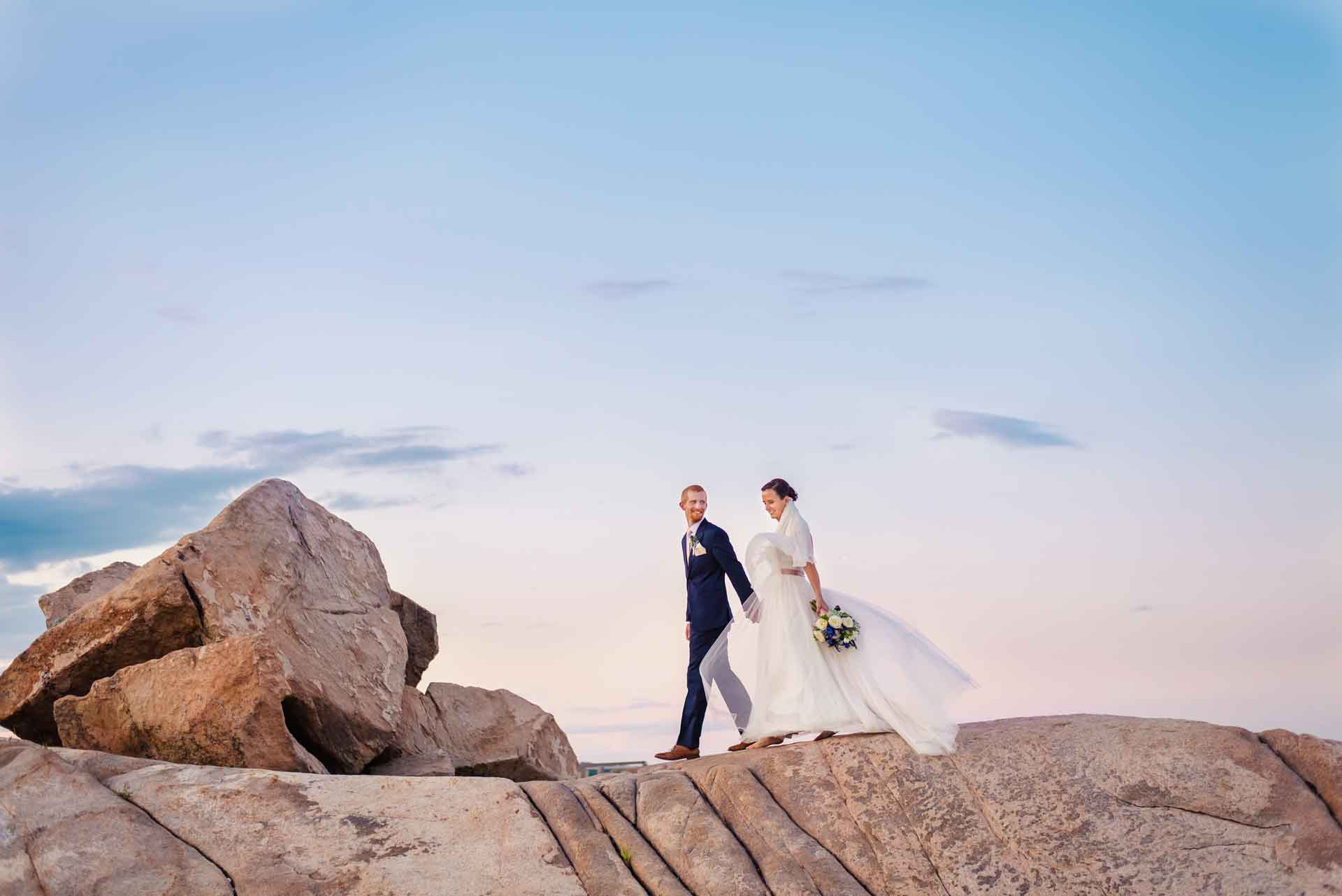 ocean side bride and grrom walking on large rocks at sunset
