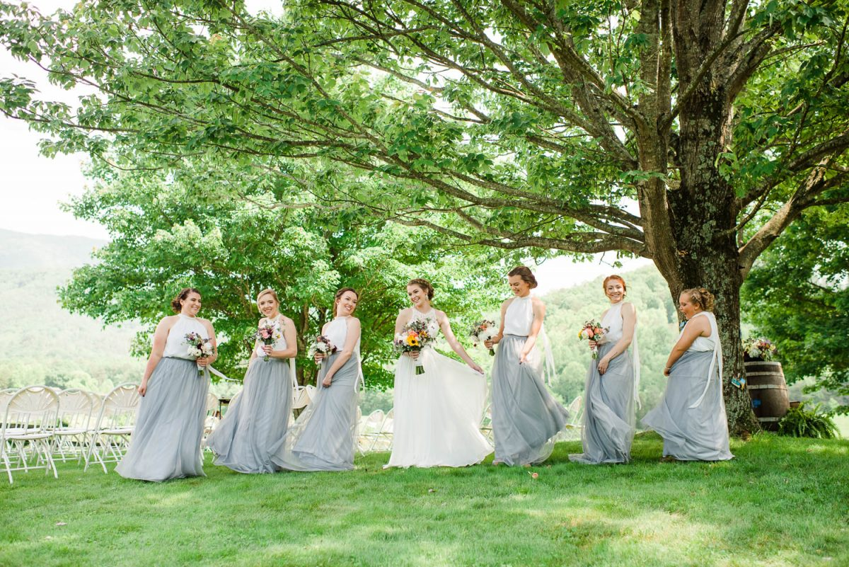 girls outside twirling in long gray dresses under a tree