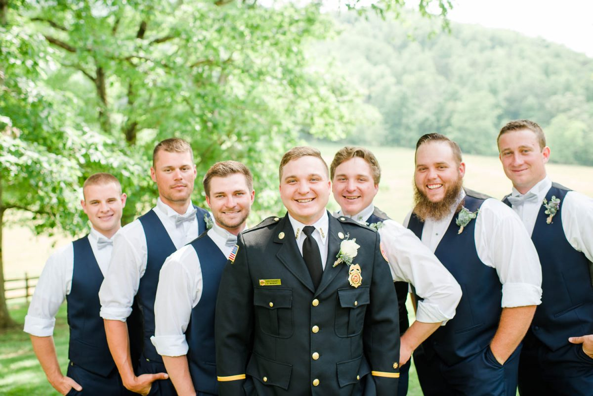 fireman groom with groomsmen in navy vests under a tree