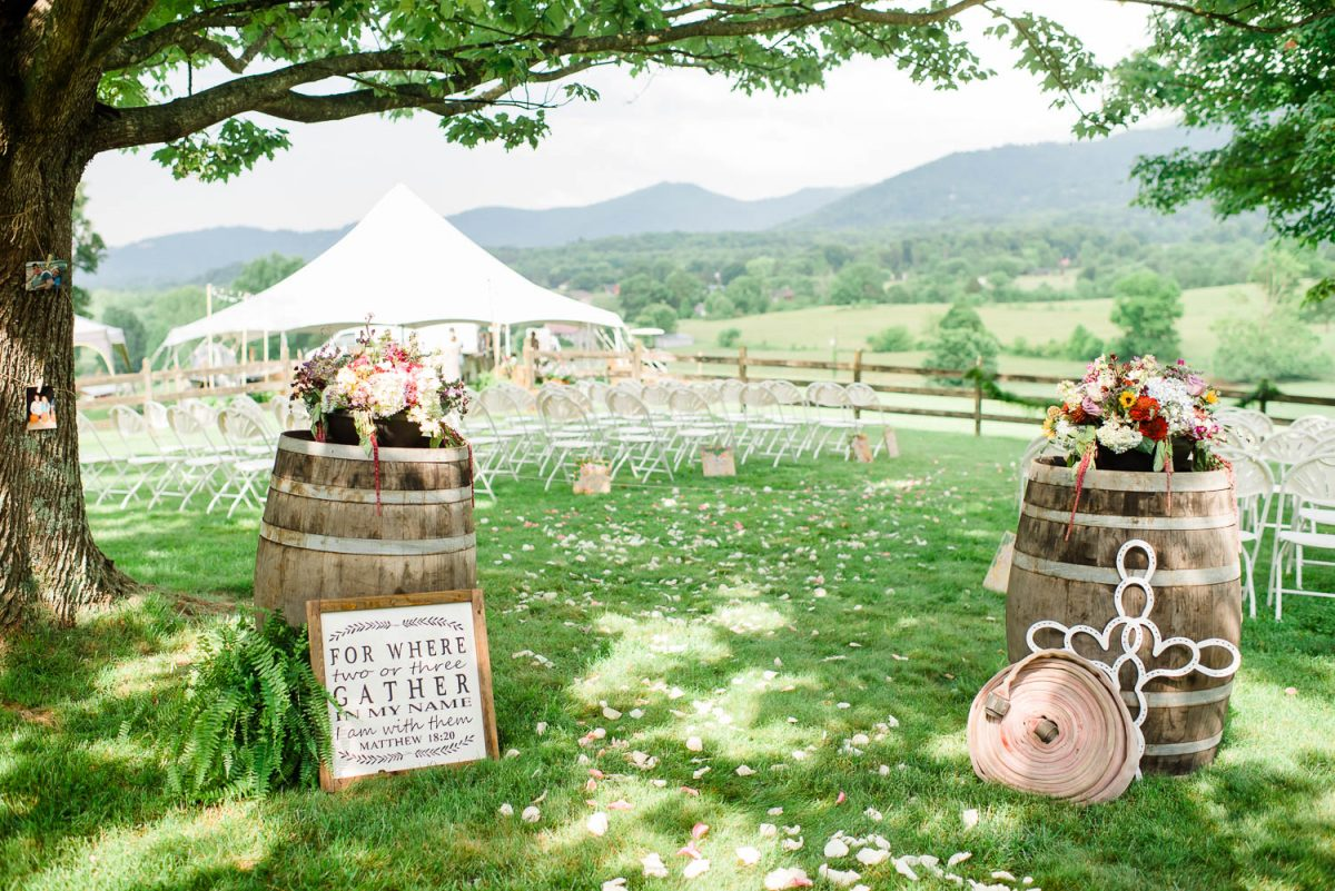 outdoor backyard wedding ceremony with whisky barrels and a vintage roll of fire hose