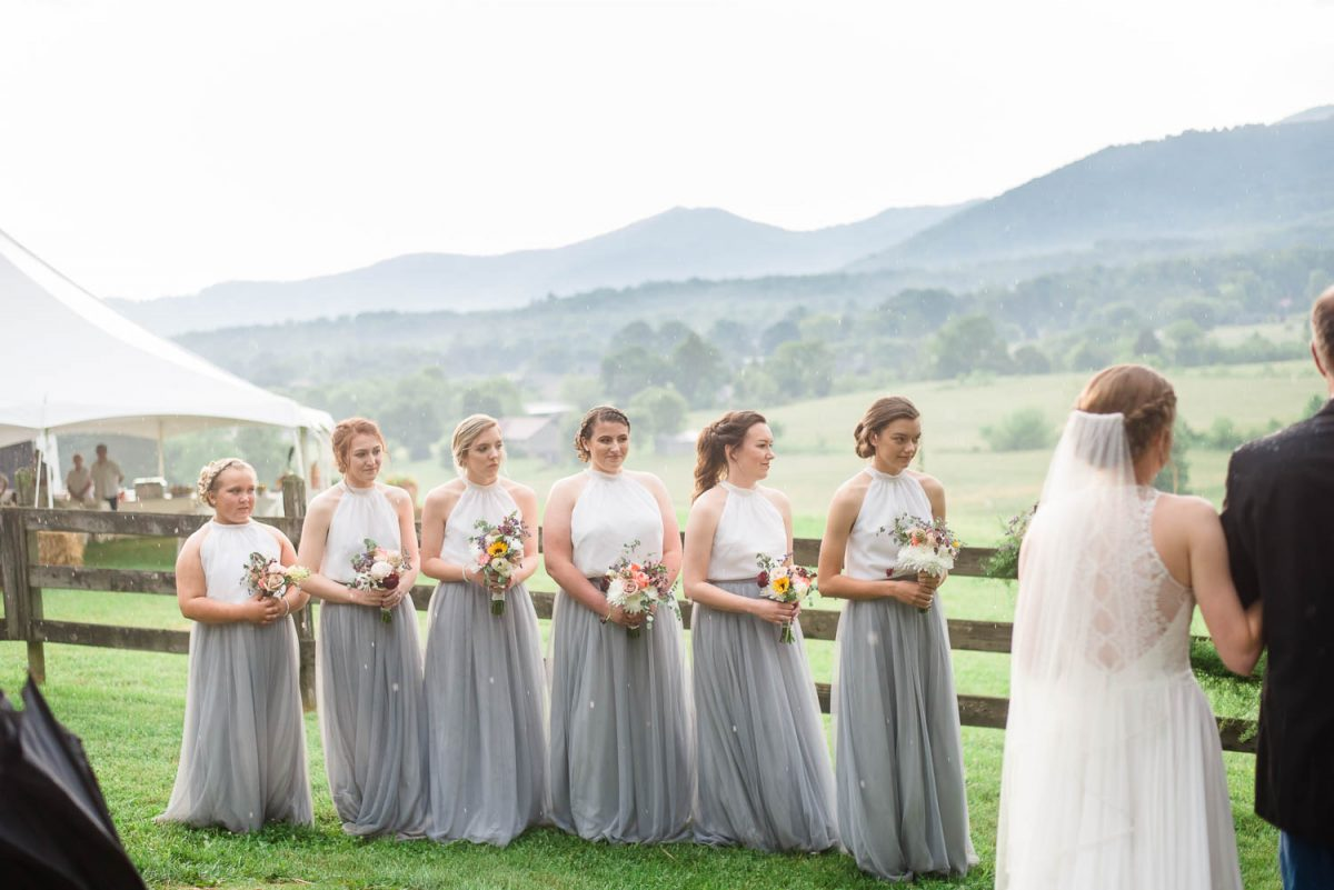 gray and white bridesmaids standing outside in the mountains