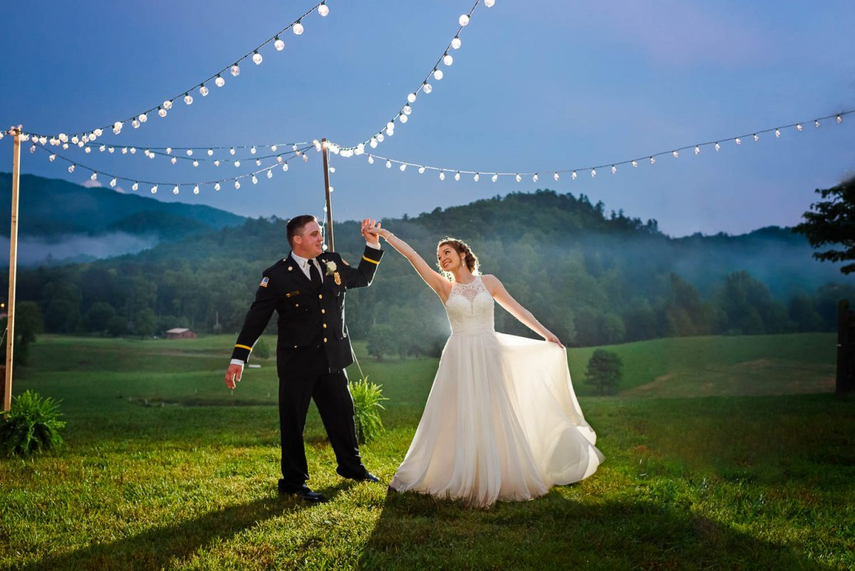 bride and groom dance outside at night at their backyard wedding