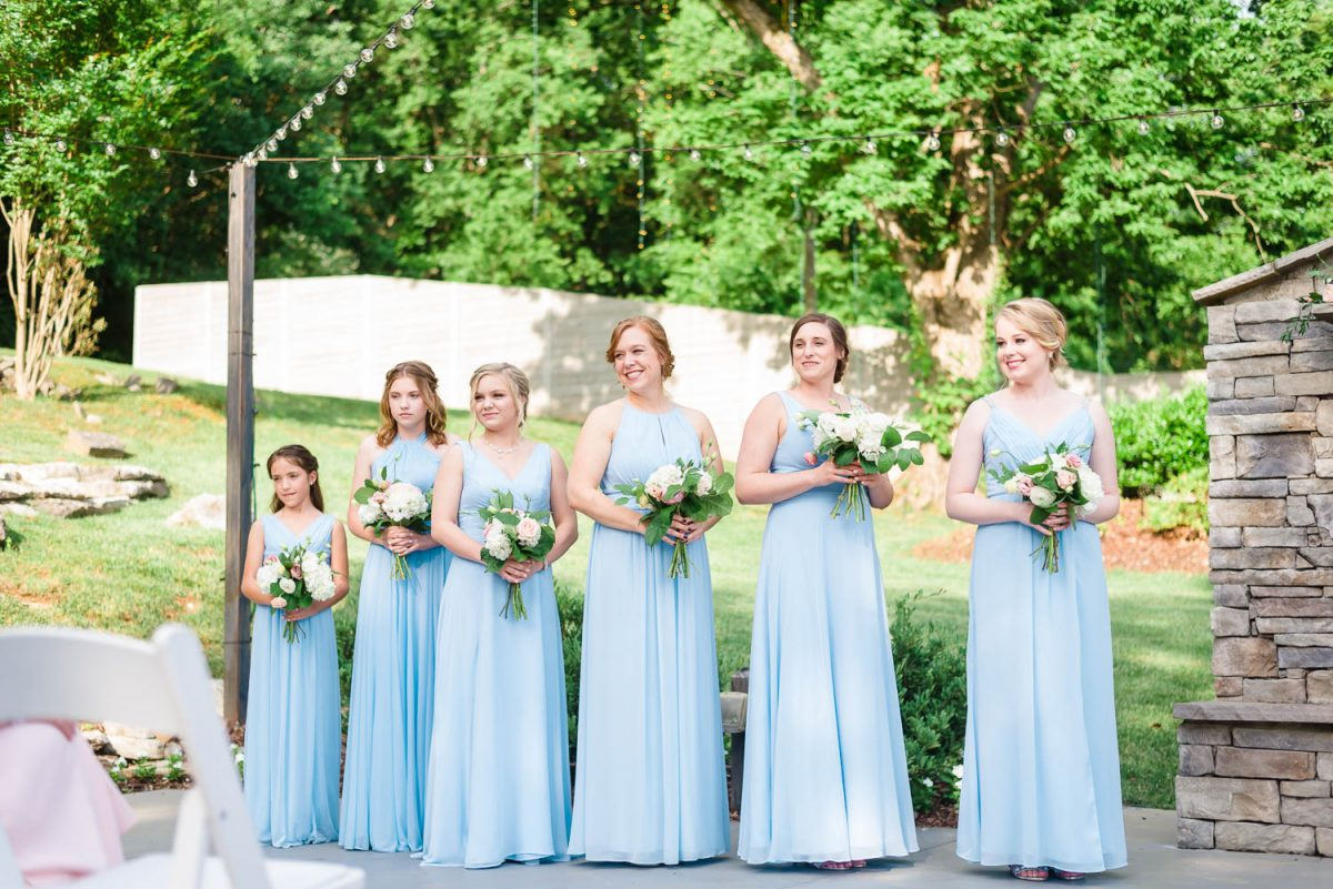 bridesmaidswearing ice blue dresses at outdoor garden wedding ceremony