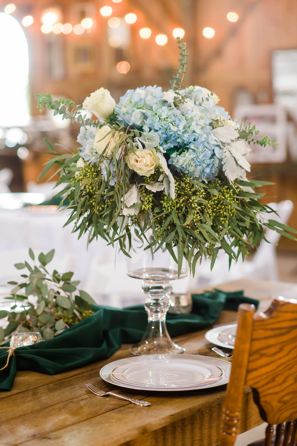 tall floral center piece with blue flowers and greenery