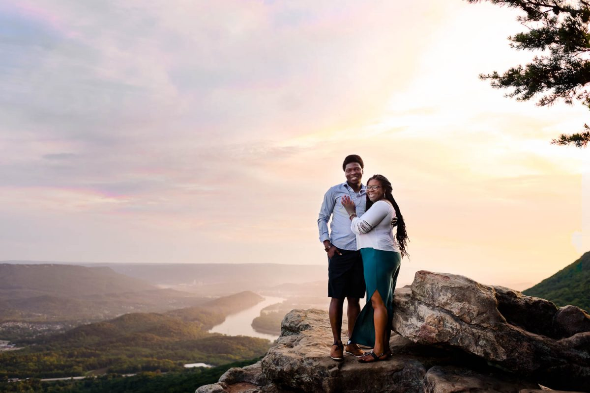 sunrising behind two engaged people on sunset rock in summer