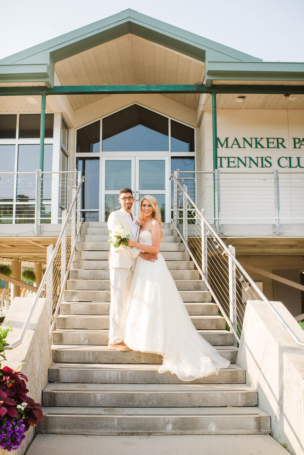 wedding couple standing on front steps at Manker Patten Tennis Club house in Chattanooga