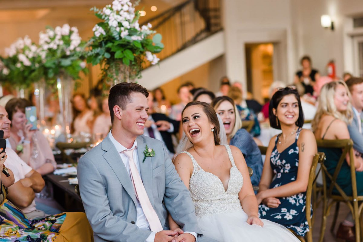 two people laughing at wedding reception