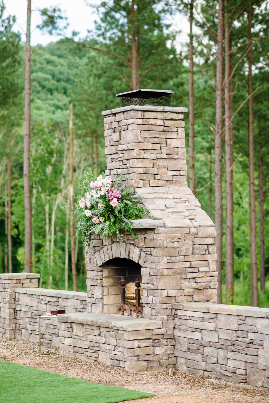 floral decor on stone outdoor fire place