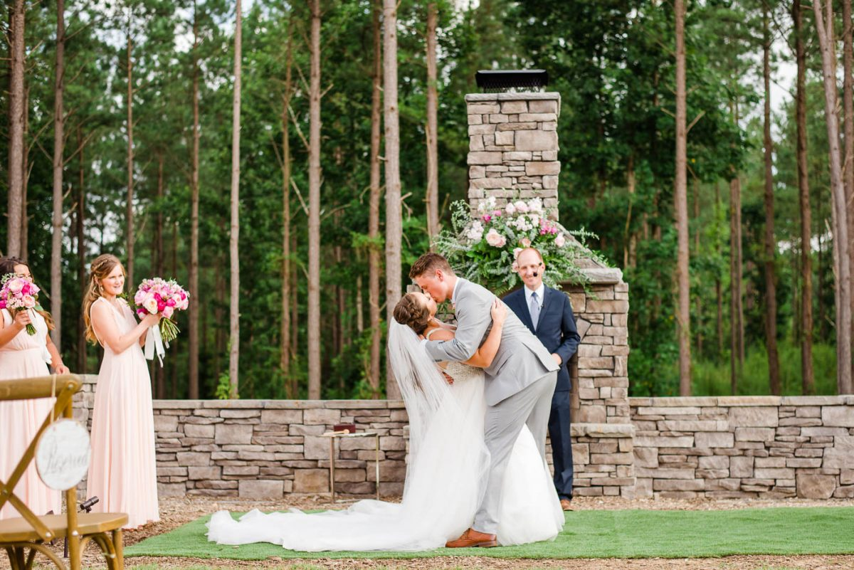 groom dipping his bride for kiss at wedding