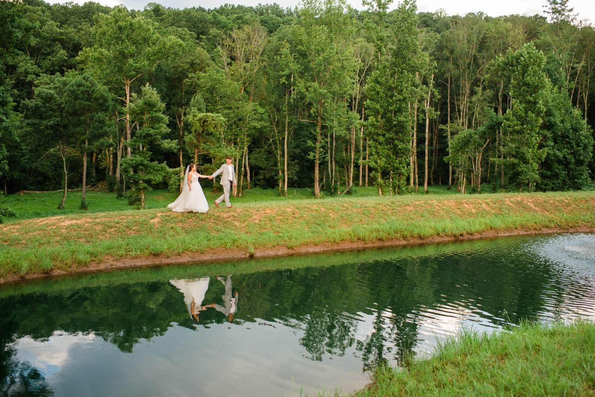 reflection of bride and groom in pond at Circle B Venue in Georgia