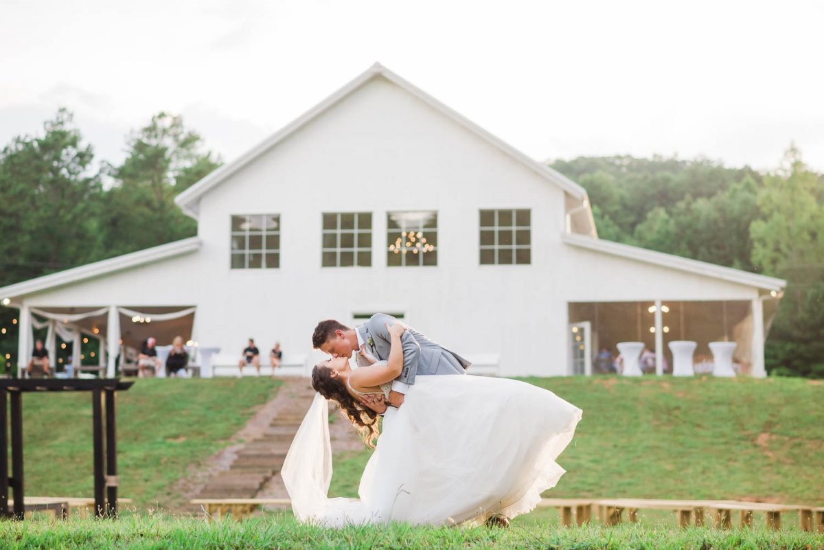 groom dipping bride in white fluffy tulle dress at their Georgia wedding