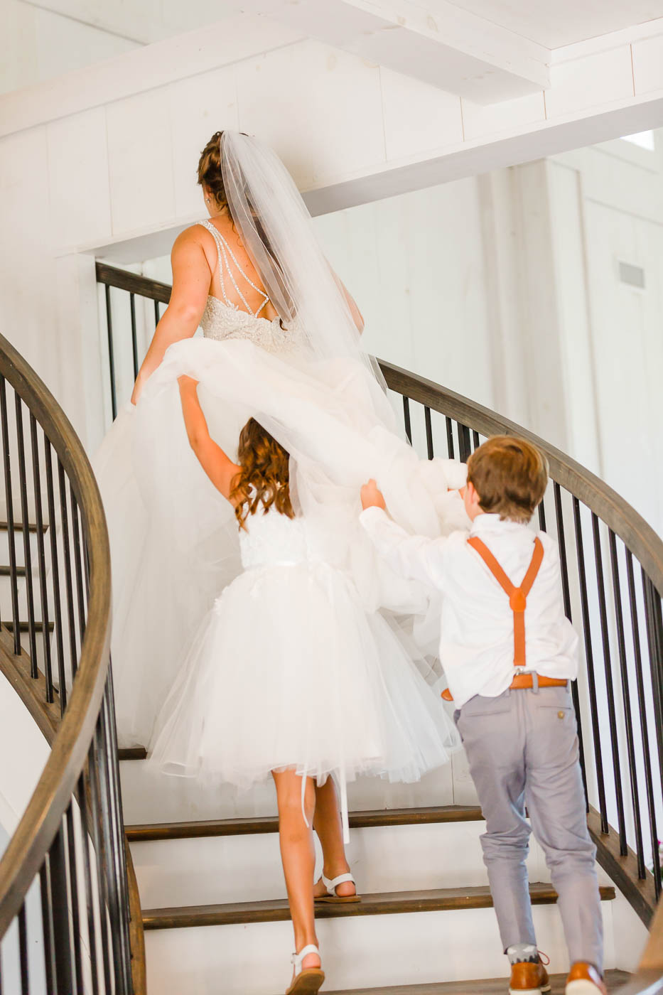 flower girl and ring bearer pushing bride up the stairs