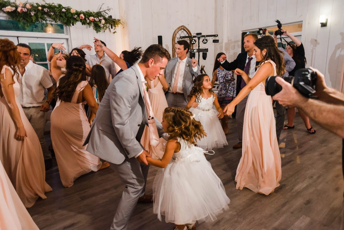 groom dancing with flower girl at wedding reception