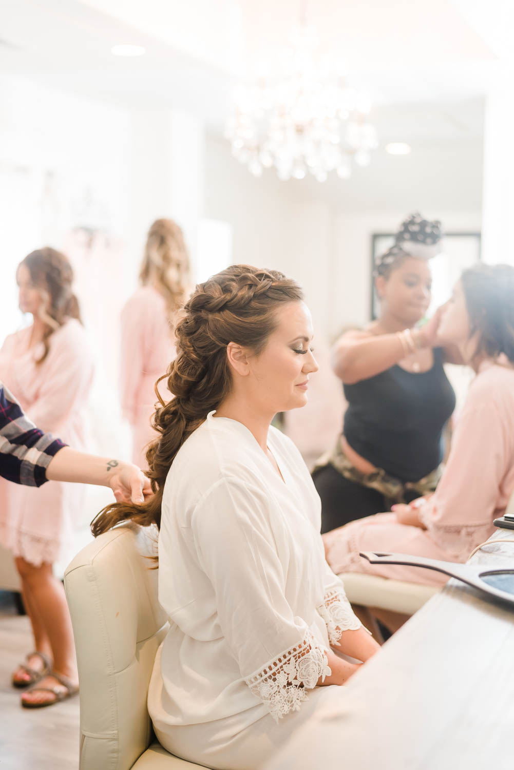 bride getting hair done on wedding day