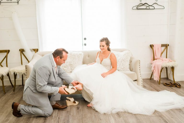 bride's dad putting on her shoes