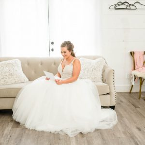 bride in white dress sitting on a couch reading a letter