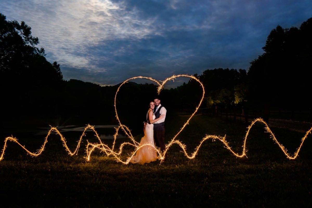 two people standing outside with a sparkler heart drawn around them outside at night in Tennessee