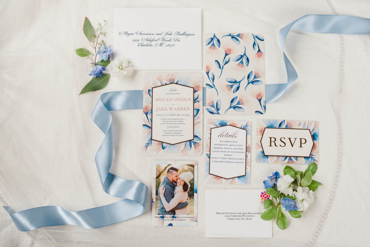 blue and pink folral wedding invitation suite with flowers and blue ribbon
