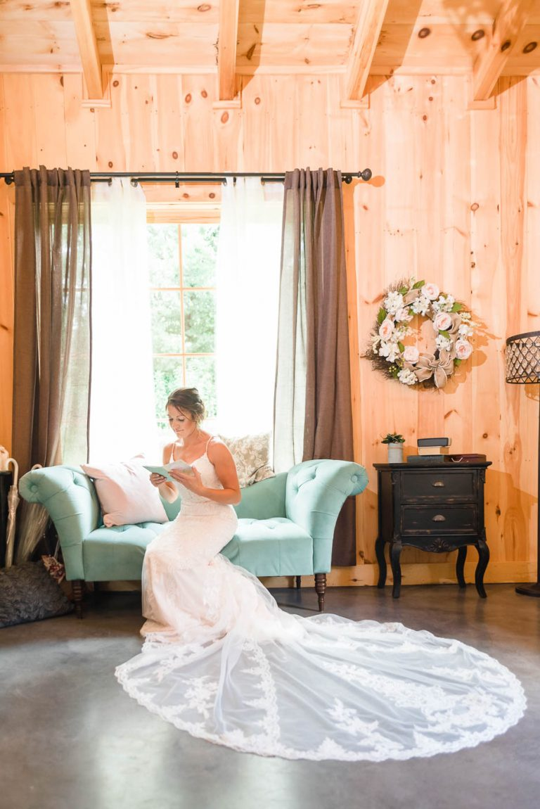 bride in a Stella York dress sitting on a green couch reding a letter