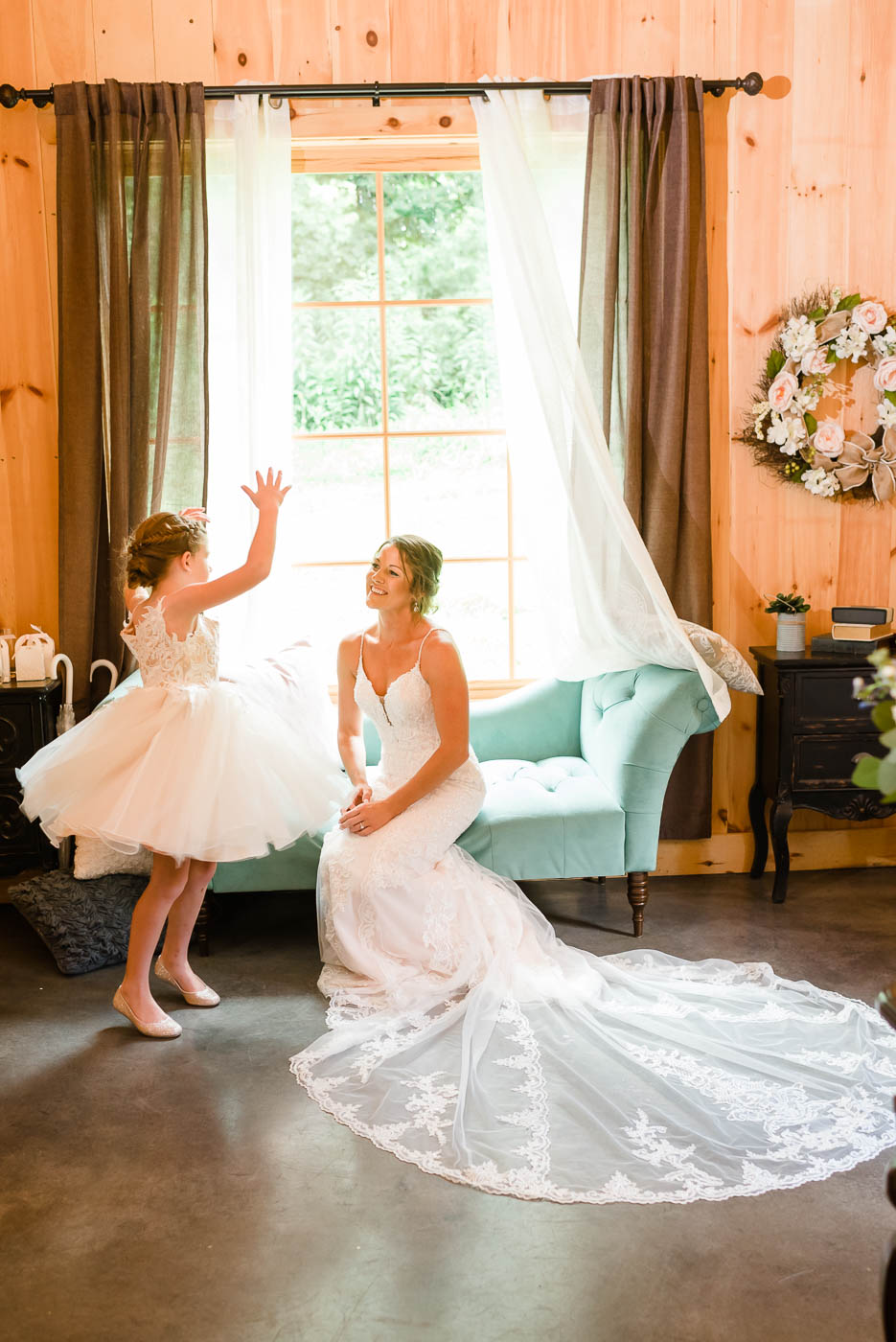 little girl in white dress talking to bride in white dress sitting on a couch