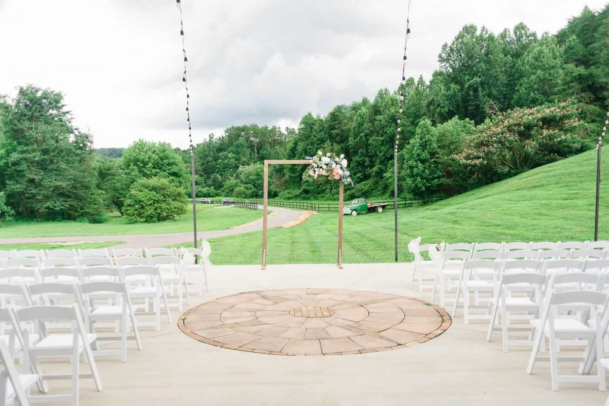outdoor wedding ceremony site with white chairs