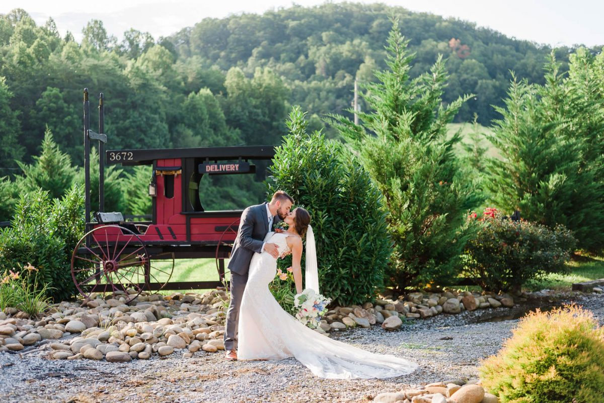 wedding couple in front of vintage red carriage in Gatlinburg