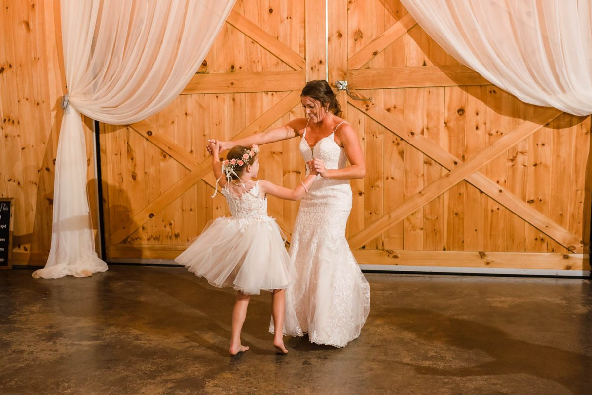 bride in Stella York Dress dancing to Polka music with small girl