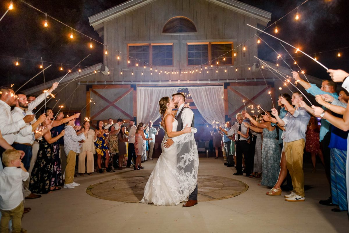 sparklers held by wedding guests as couple kisses