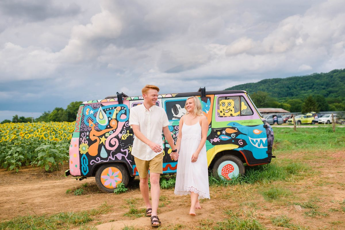 two people both wearing white in front of vintageVW buss painted in wild colors