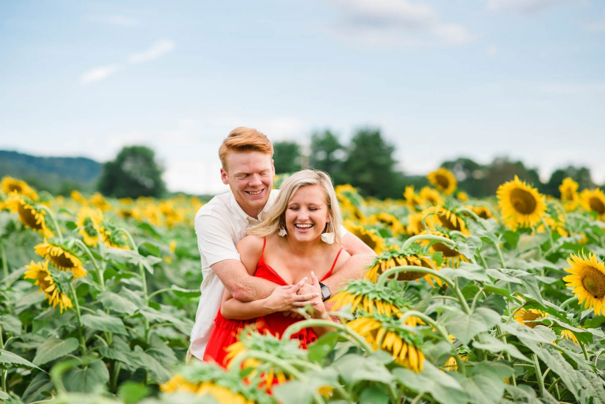 two people laughing out in a sunflower field in Tn