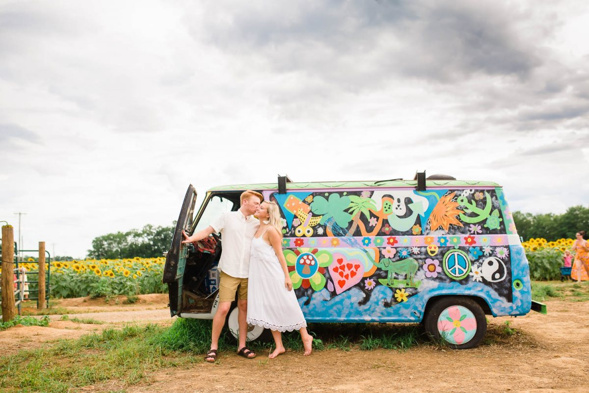 girl wearing white sundress kissing fiance in front of a brightly colored VW buss