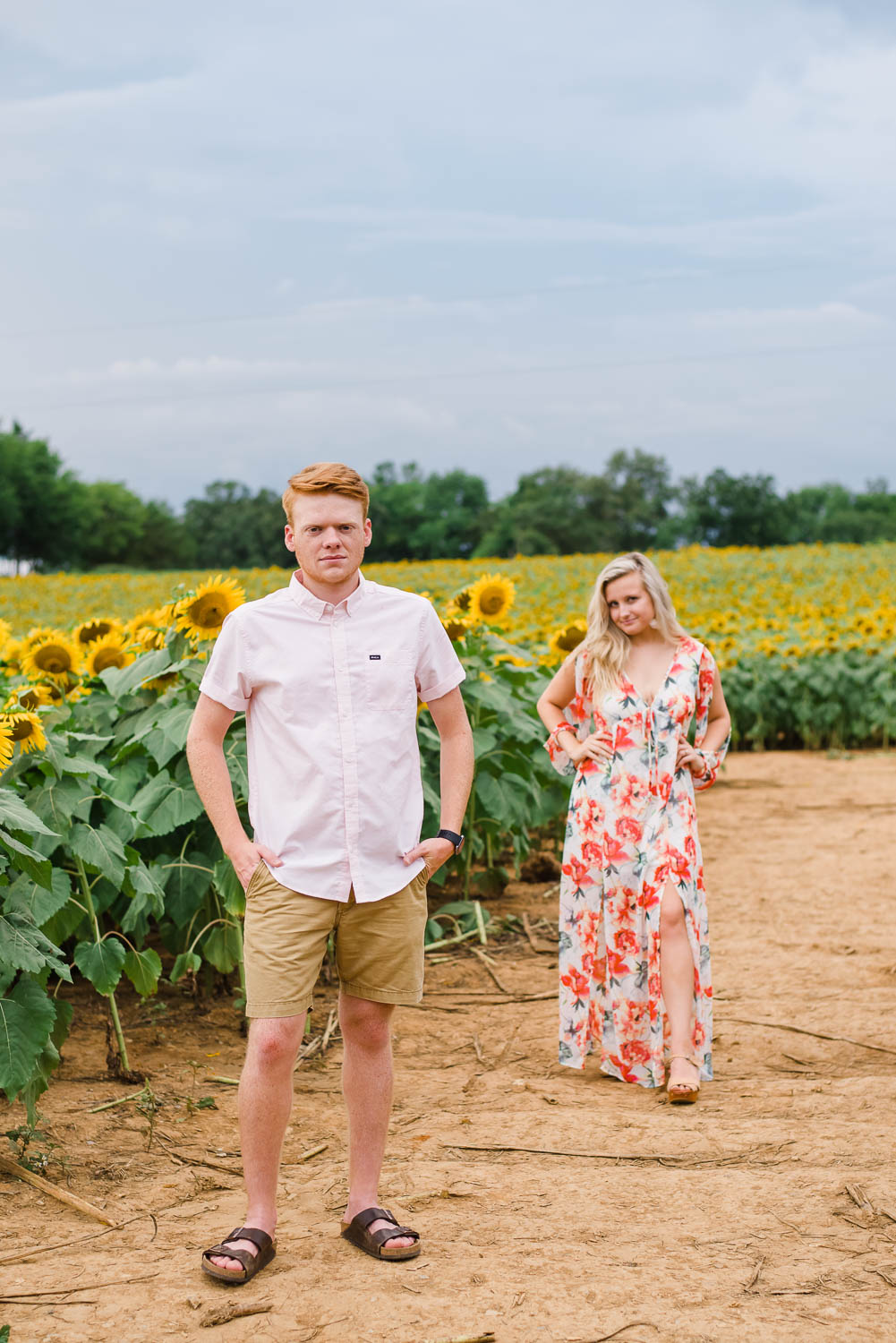 two people in sunflowers field with one standing close to camera and the other off in the distance