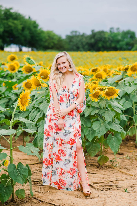woman in orange floral dress in sunflower field