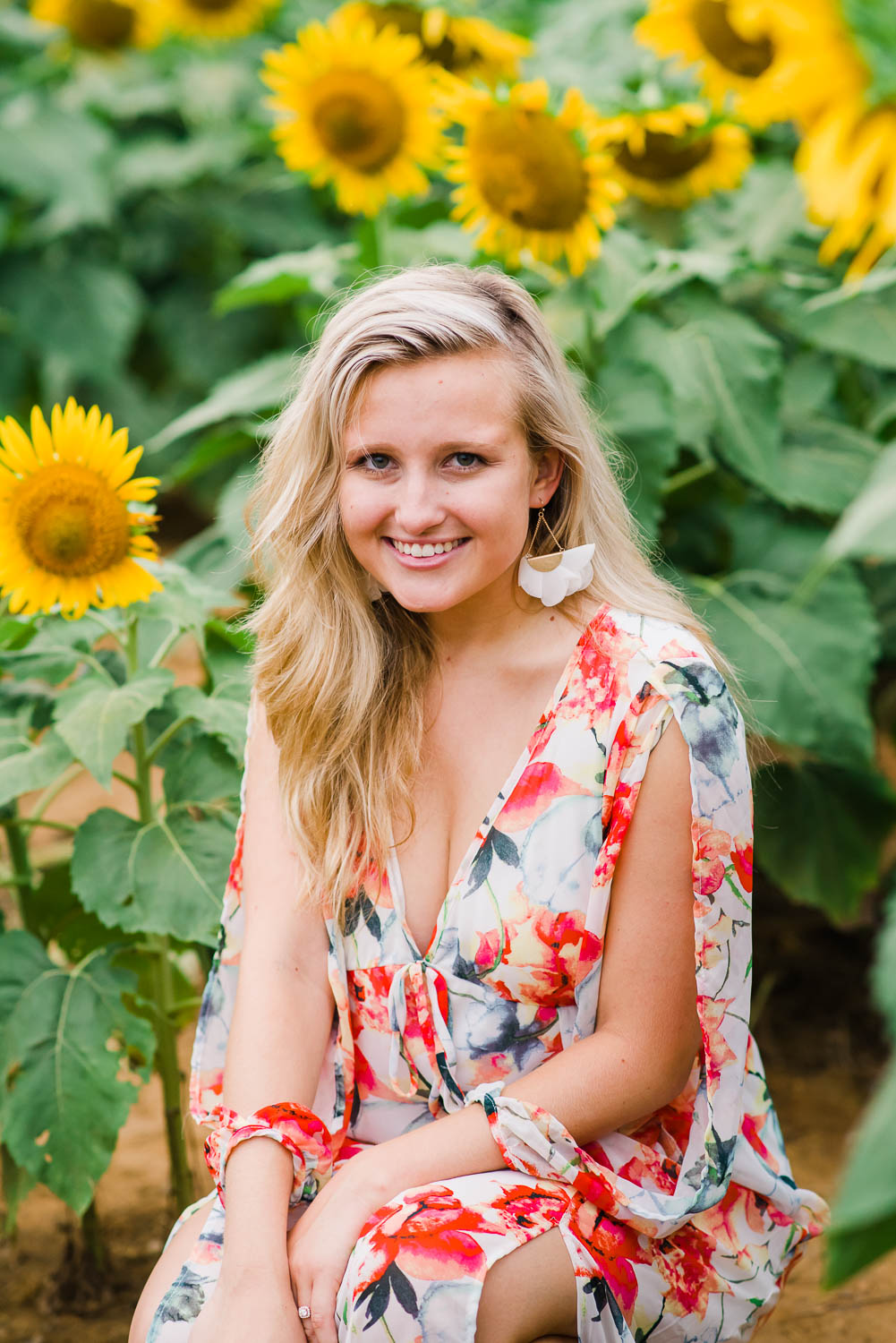 blonde girl sitting in among sunflowers in Ooltewah Tn