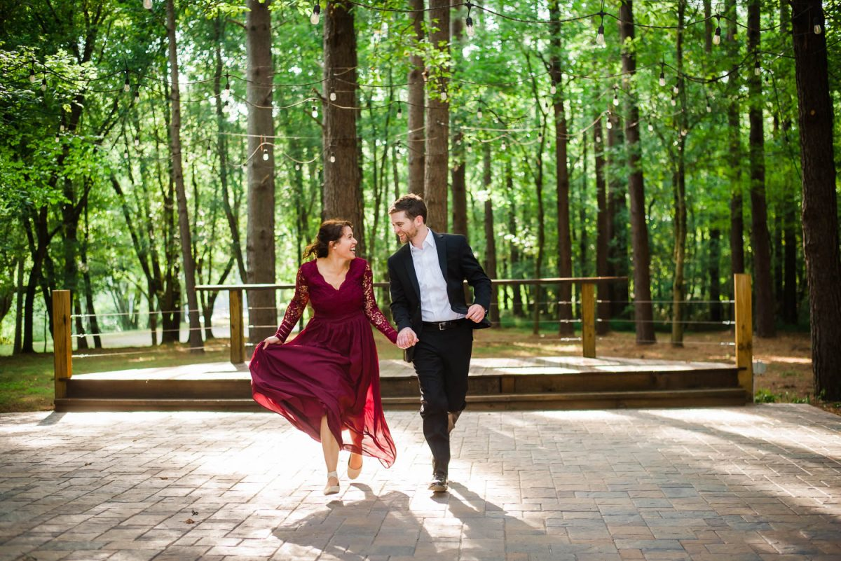 girl in maroon dress and guy in black suit running in the forest