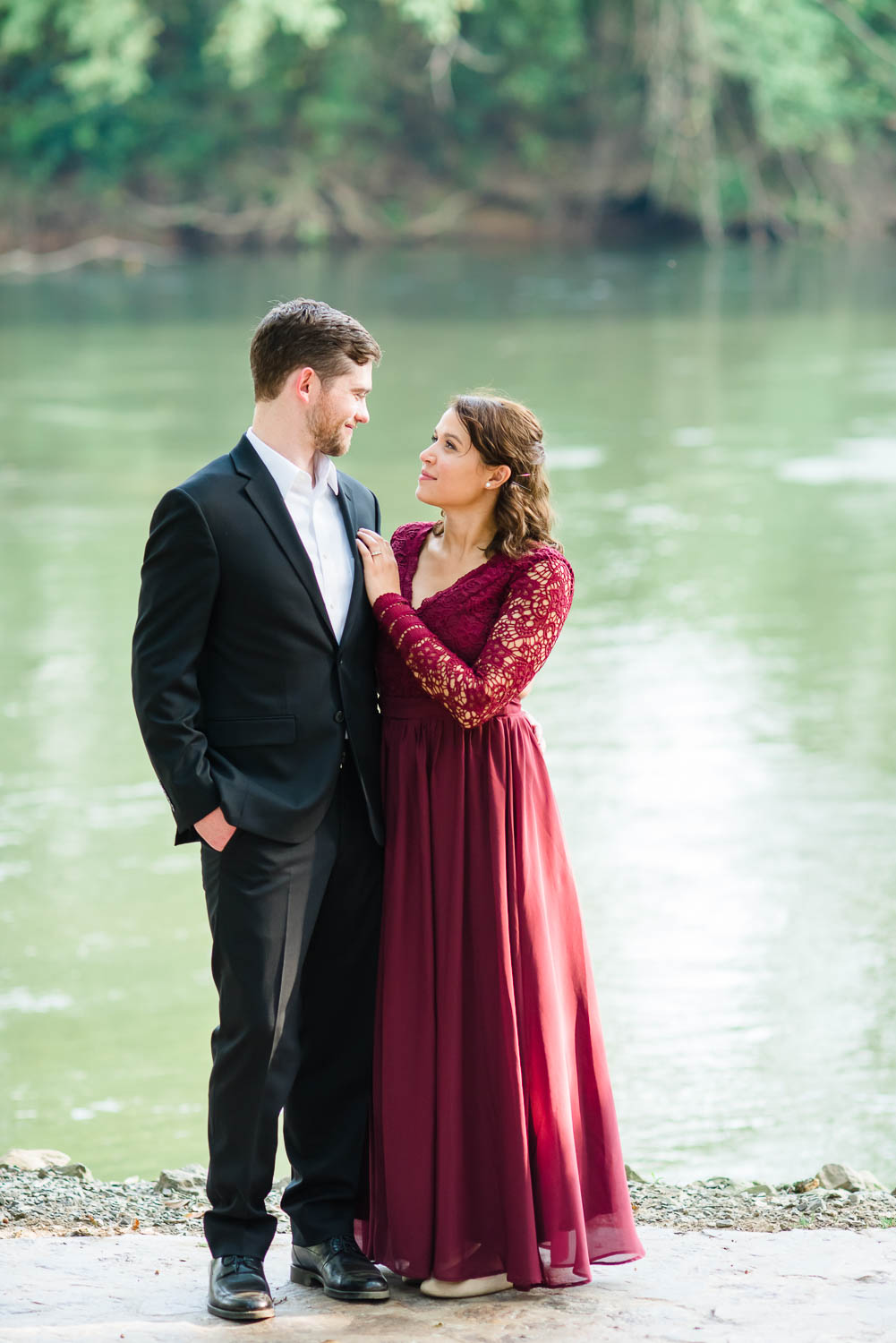 guy wearing a blacksuit and a girl wearing a maroon dress with lace sleives